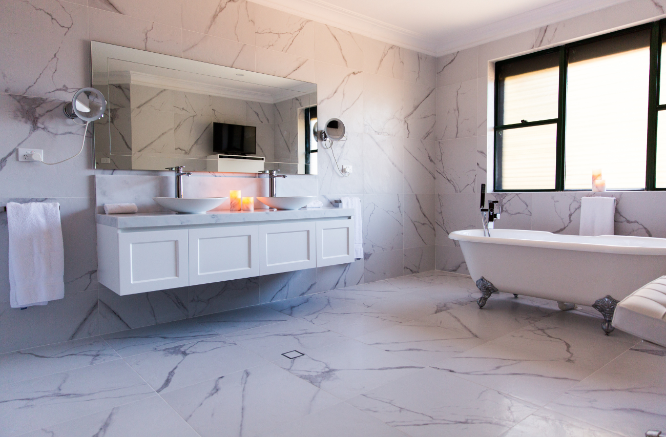 3/4 angle shot of a luxury residential marble bathroom in Chatswood, Sydney by Renovahouse with marble tiled walls and floors and freestanding bathtub.