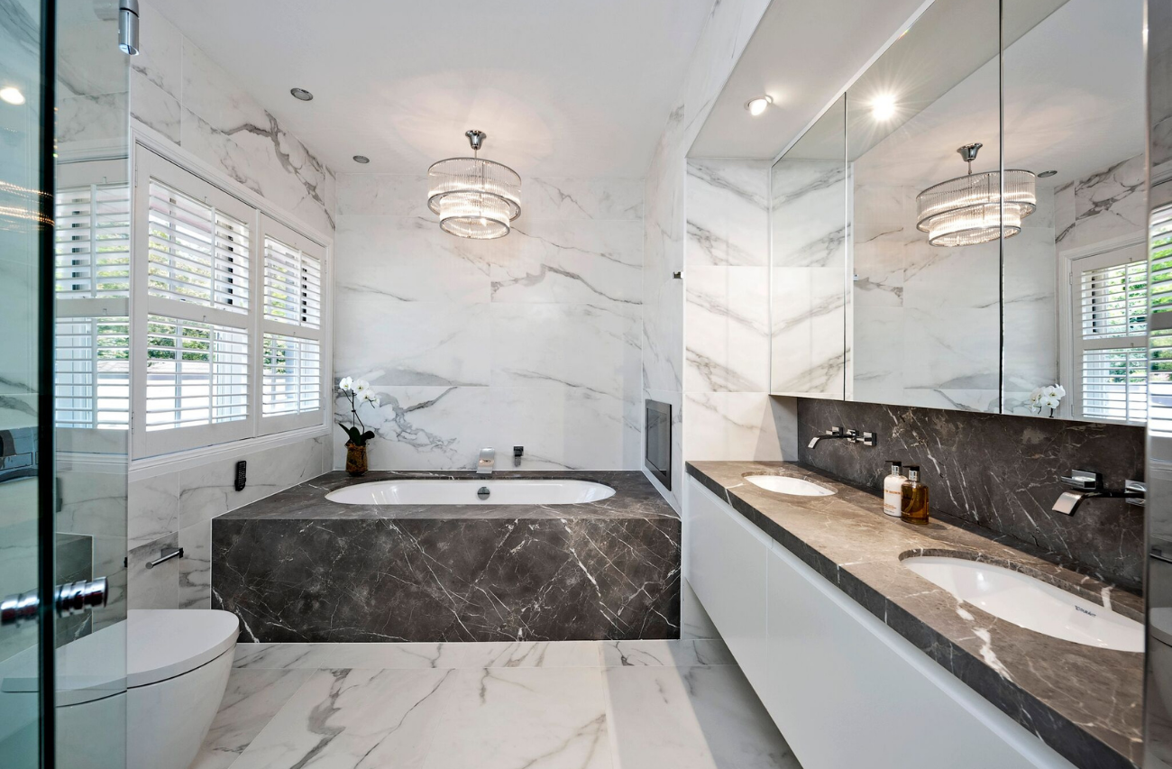 Wide shot of a marble bathroom in Turramurra, Sydney by Renovahouse with marble tiled walls and floors and under-mount bathtub.