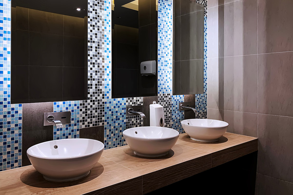 This photo of a Commercial Bathroom in Lindfield Sydney NSW by Renovahouse shows just how important it is to have the right lighting in a luxury bathroom. These LED strip lights behind the mirrors make the mosaic tile patterns come to life.