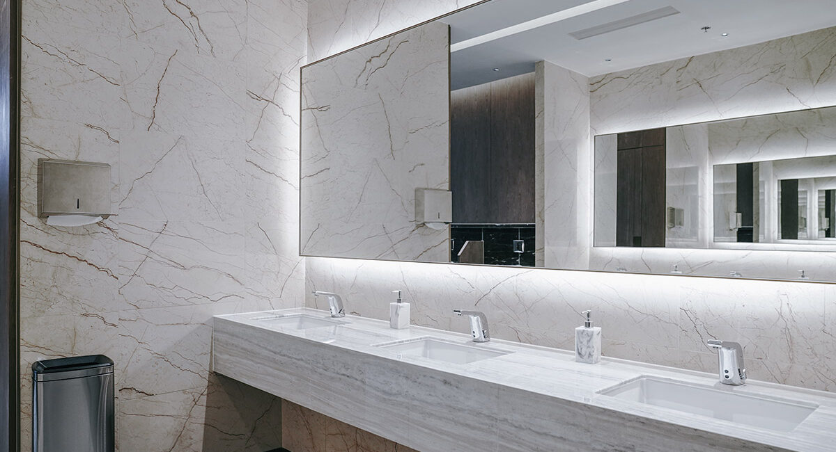 This is a photo of the marble finish on the sink and vanity units in a luxurious commercial men's bathroom installed and designed by Renovahouse in North Sydney