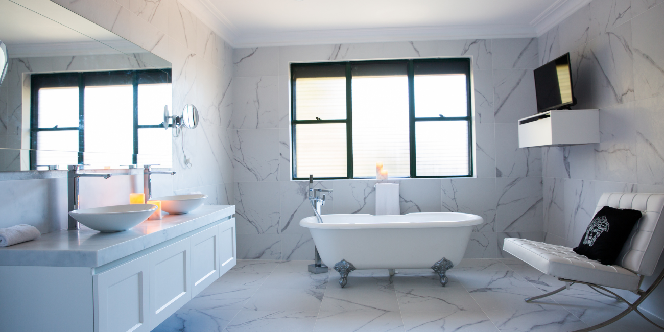 Wide shot of a luxury residential marble bathroom in Chatswood, Sydney by Renovahouse with marble tiled walls and floors and freestanding bathtub.