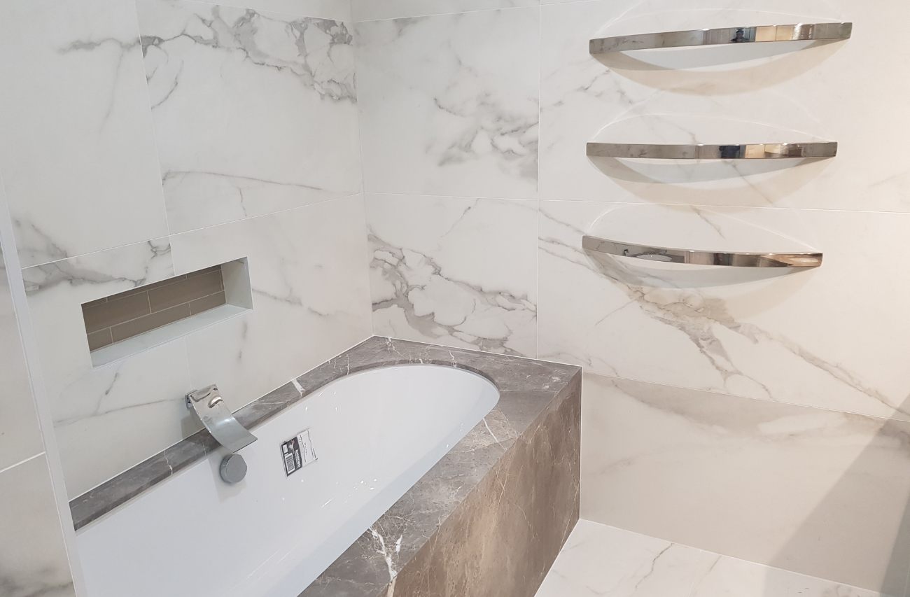 Close up of a marble bathroom in Turramurra, Sydney by Renovahouse with marble tiled walls and floors and under-mount bathtub.