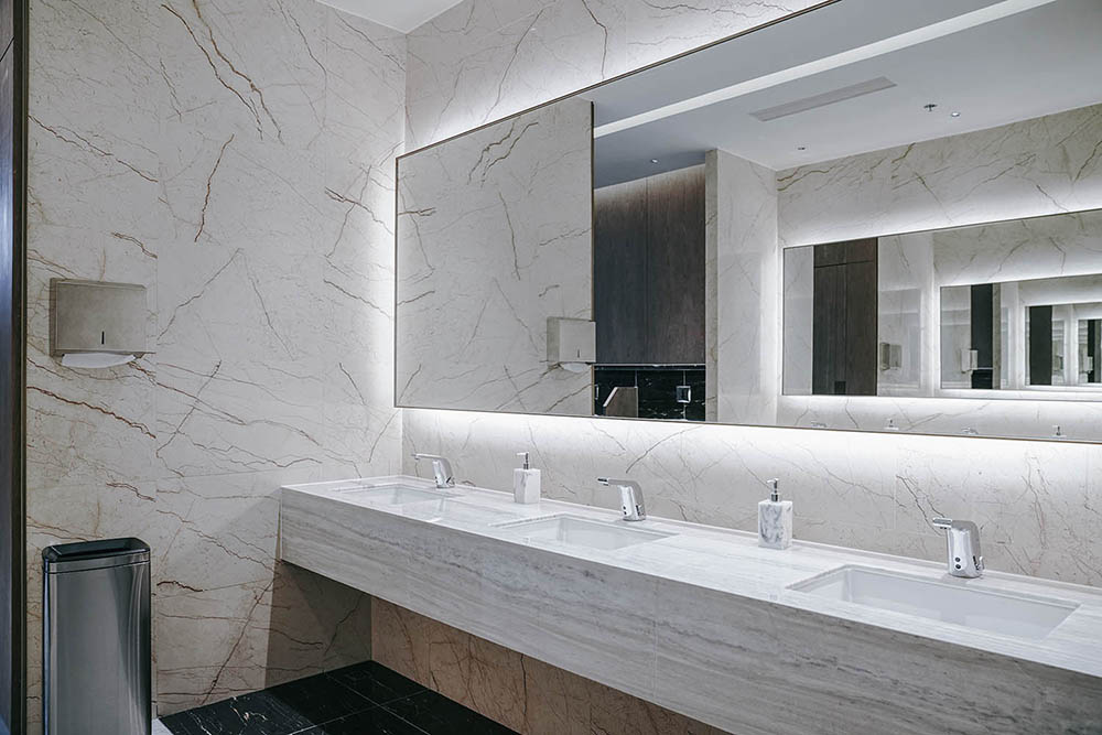 Black and White Commercial Bathroom by Renovahouse Sydney with grey marble vein and one piece mirror