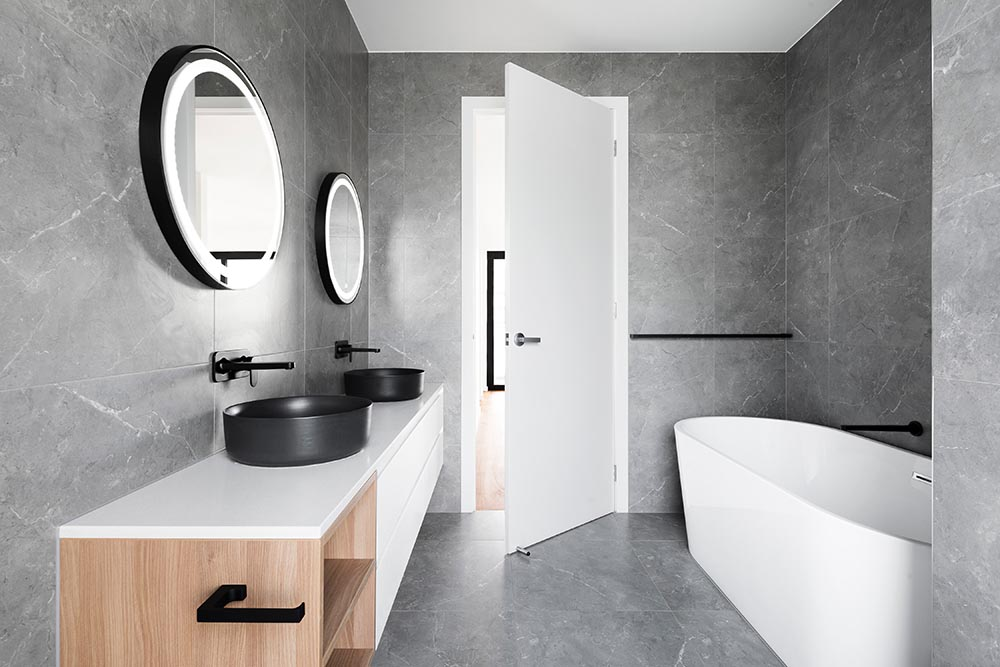 This European style bathroom has a stunning black and white theme with an elegant freestanding bathtub that is a feature in Renovahouse interior designs in Sydney