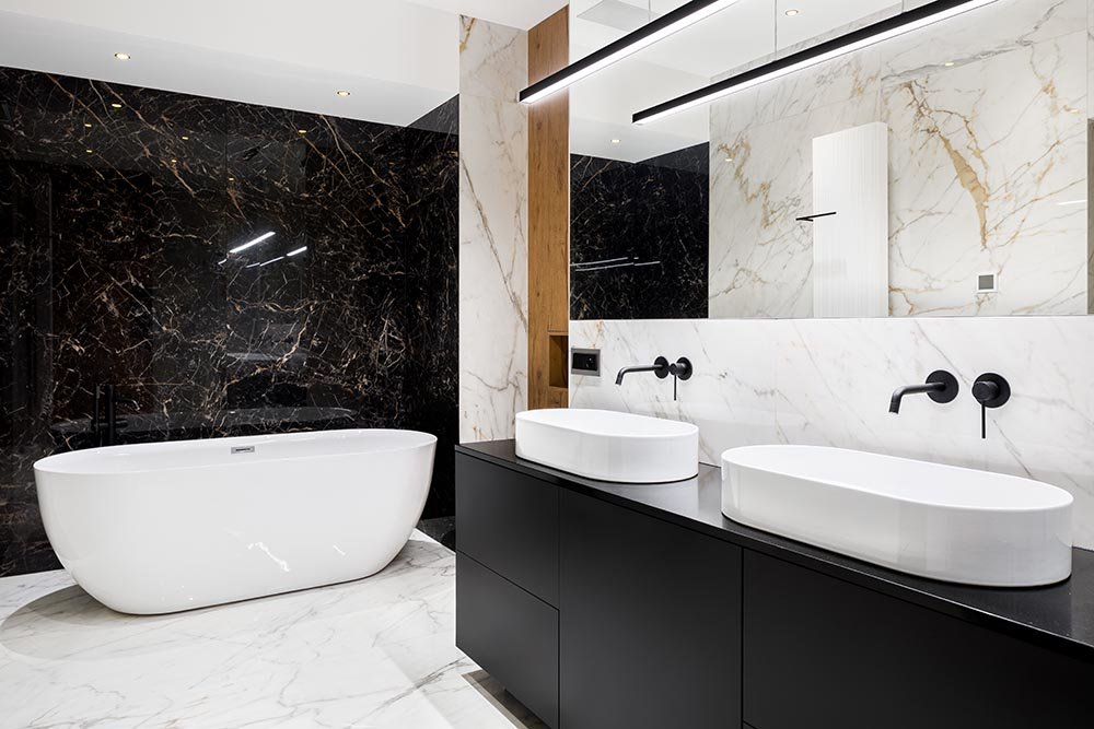 This luxury bathroom by Renovahouse in Sydney uses the beige vein in the marble walls and floor to match the timber feature panel in the wall