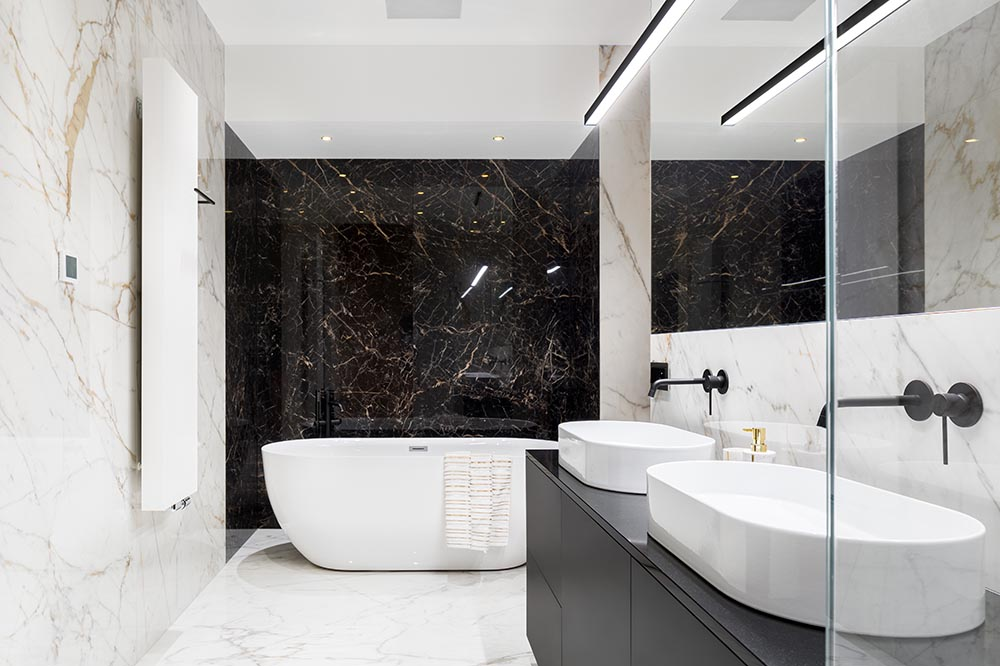 A classic and elegant marble tiled black and white bathroom with high gloss finishes and matt black tapware is simply stunning. Completed by Renovahouse in Sydney
