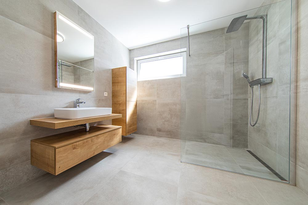 This spacious bathroom by Renovahouse in Sydney uses the flat matte finish of the grey wash tiles to tie in perfectly with the timber cabinetry