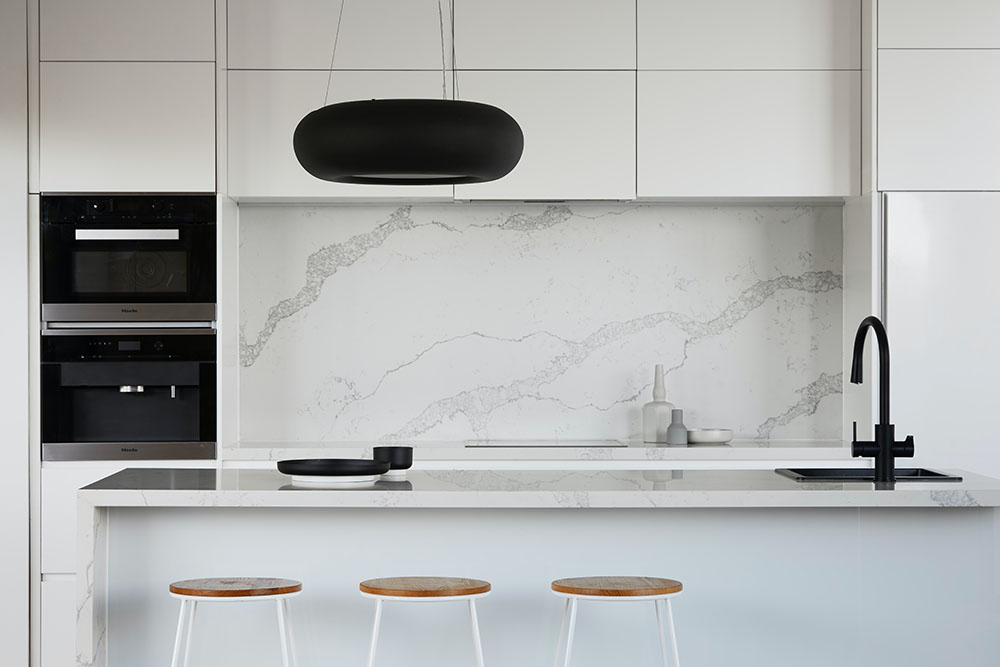 This black and white luxury kitchen in Sydney by Renovahouse has a marble splash back and twin wall ovens with matt black feature pendant light