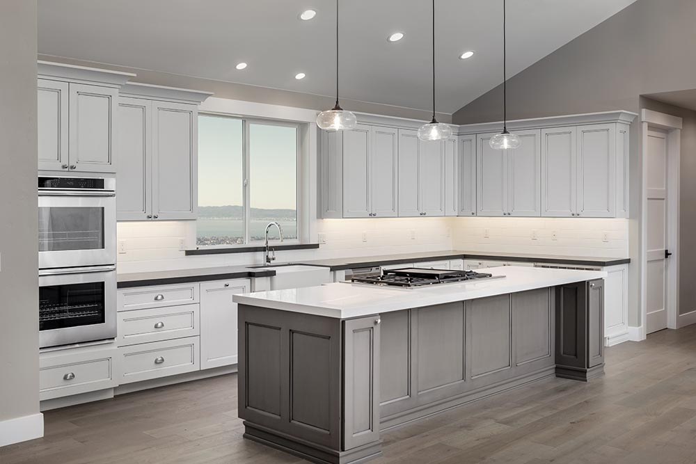 This large white shaker style kitchen by Renovahouse features a great island with cook top and lime-wash timber floors