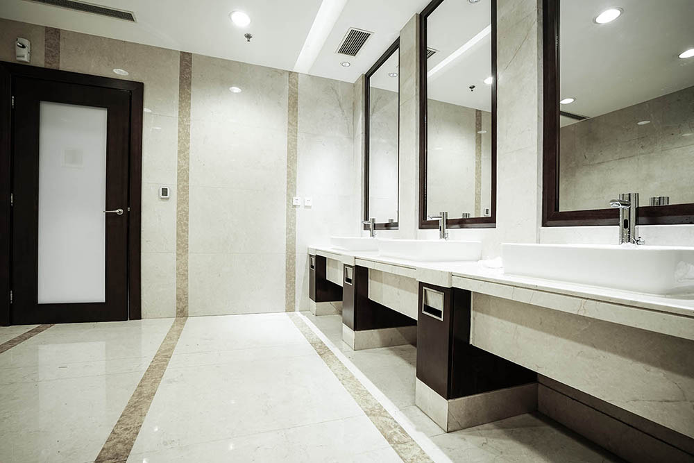 The strip feature tiles in this Commercial Bathroom by Renovahouse in Sydney accentuate the long lines provided by the sleek benchtop under the luxury handwash basins and stainless steel tapware