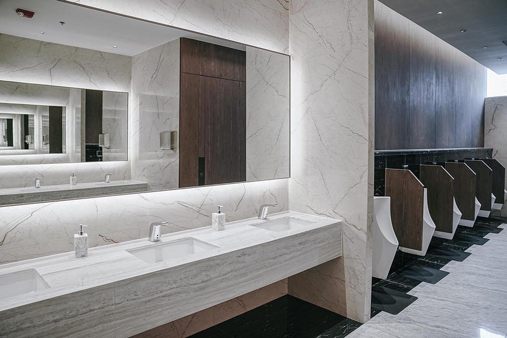 Italian Milan styled luxurious commercial bathroom in Sydney by Renovahouse with marble tiles and timber partitions between the unique bathroom fixtures
