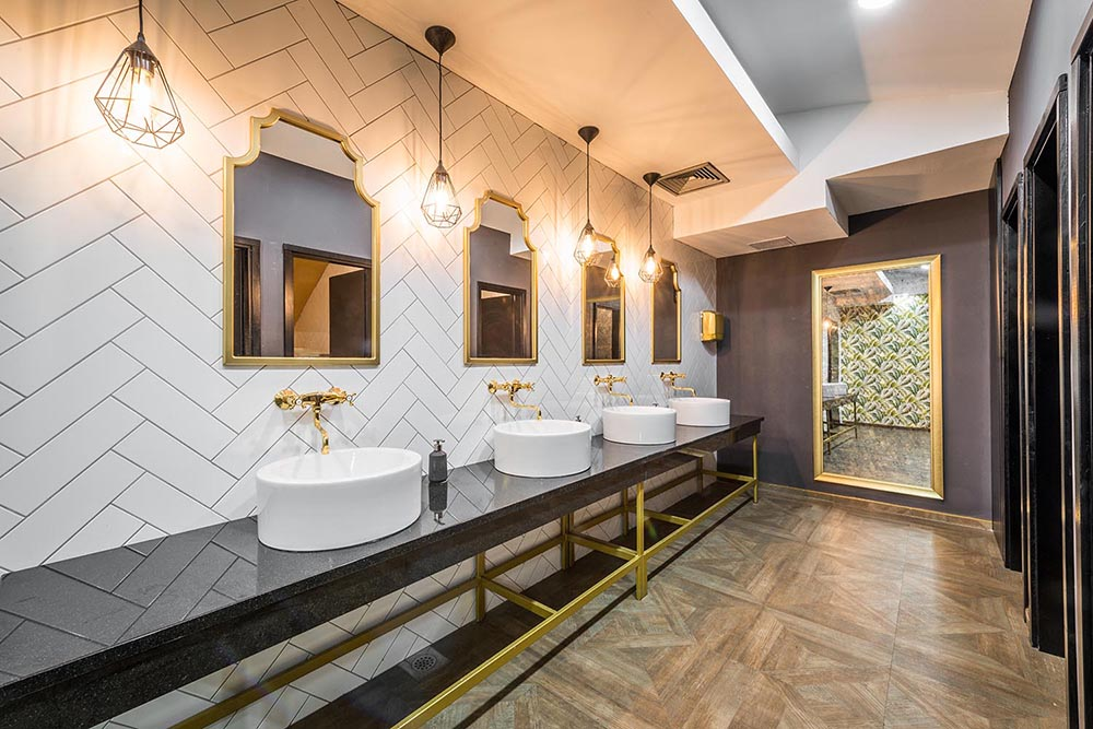 Another stunning classic commercial bathroom by Renovahouse in Sydney features herringbone white wall tiles that provide a wonderful backdrop to the classic gold-trimmed mirrors and tapware.