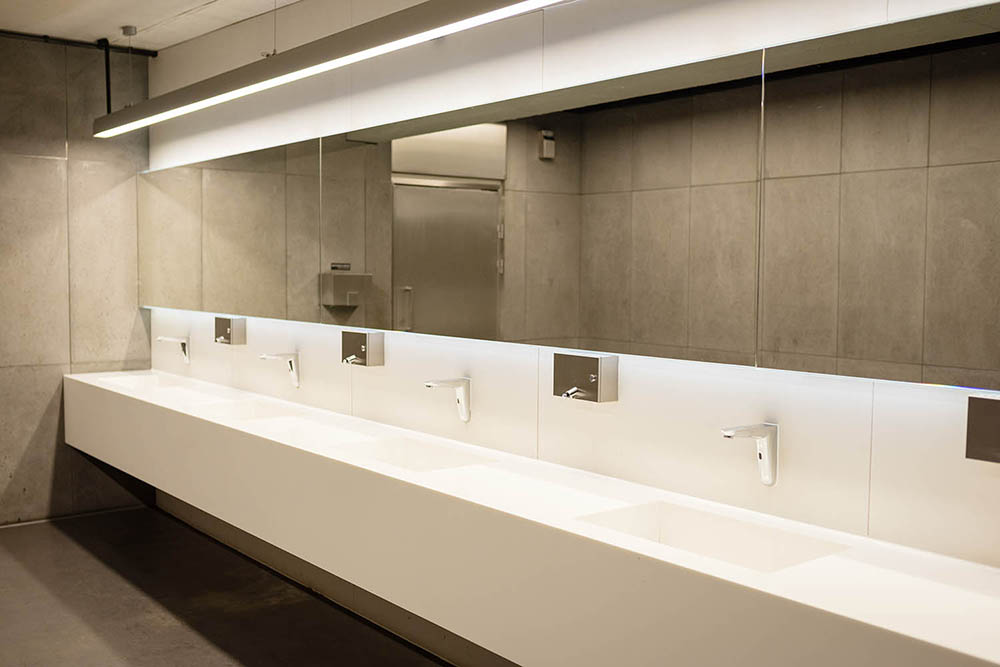 Another beautiful and luxurious commercial bathroom by Renovahouse in Sydney features long lines accentuated by the vanity benchtop with integrated sinks and wall mirrors that feel like they extend out from the rear LED lights