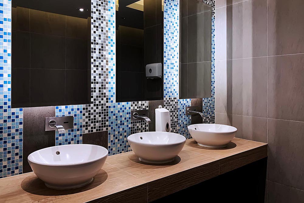 3/4 quarter angle image of this symmetrical commercial bathroom by Renovahouse in Sydney with blue mosaic tiles and feature lighting behind the mirrors