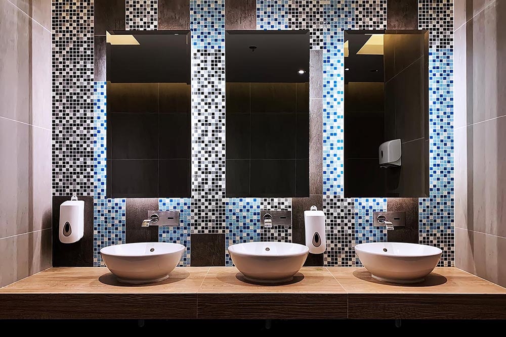Three columns of perfect symmetry in this commercial bathroom by Renovahouse in Sydney with blue mosaic tiles and feature lighting behind the mirrors